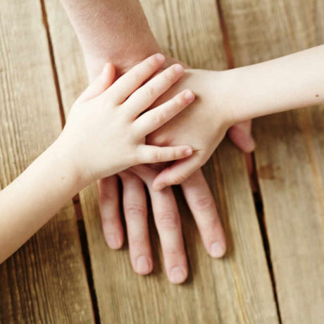 Hands of kids on that of their father